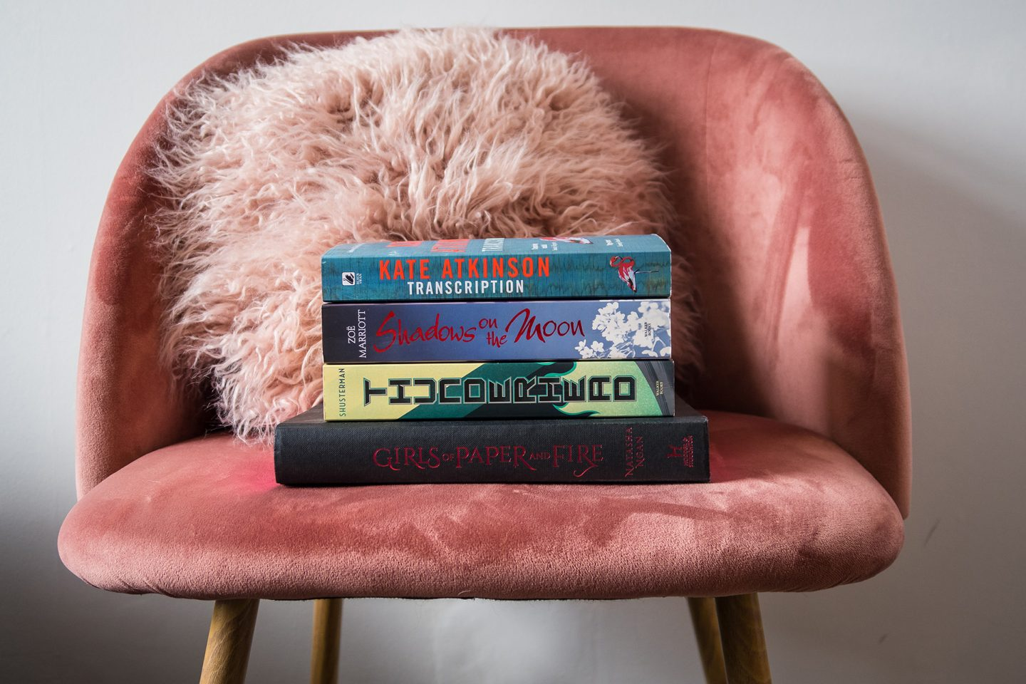 Books stacked on pink velvet chair