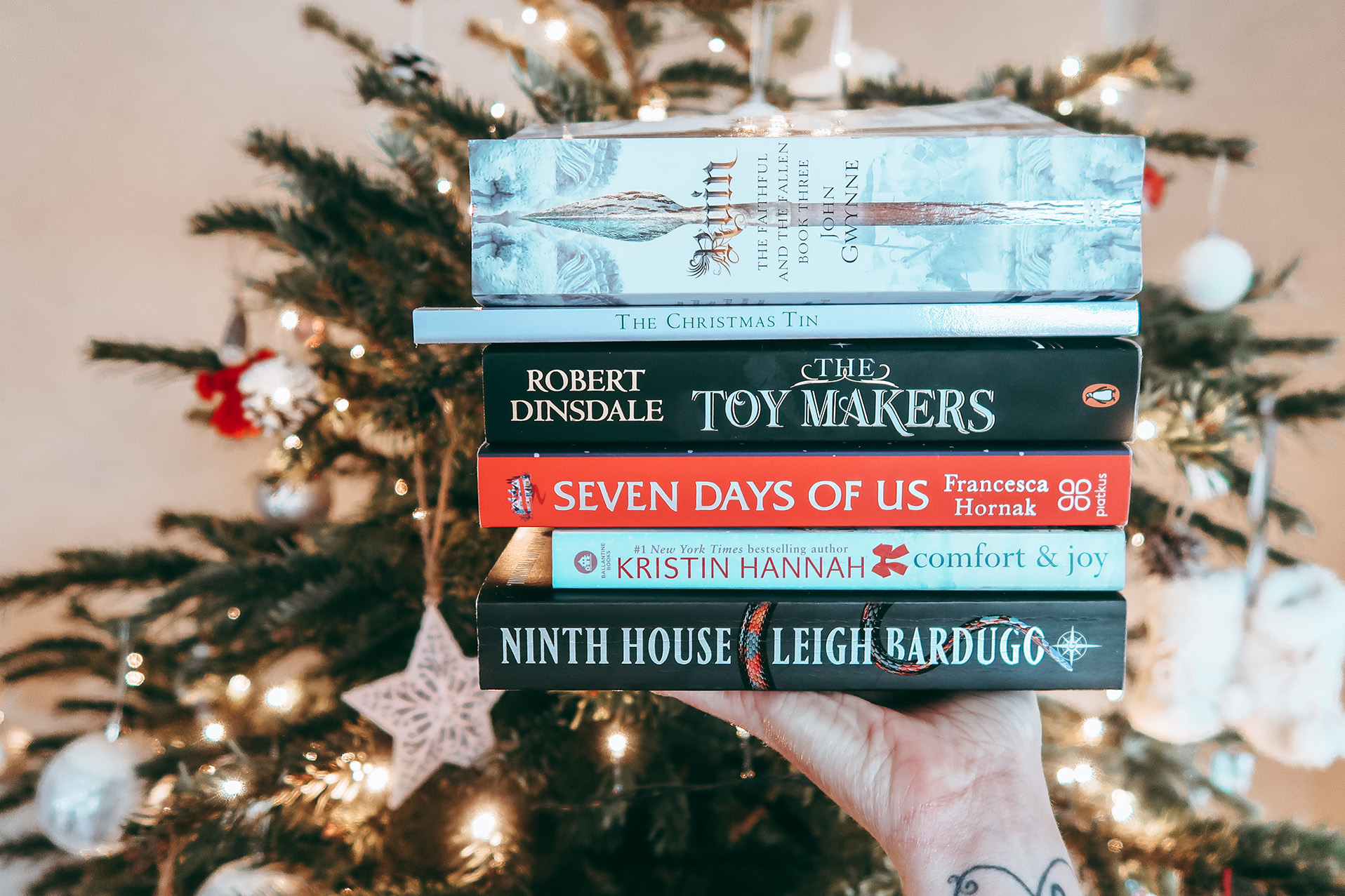 stack of books in front of christmas tree
